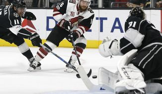 Los Angeles Kings center Anze Kopitar, left, of Slovenia, gets his stick on the puck to stop Arizona Coyotes left wing Max Domi, center, against goalie Ben Bishop, right, during the first period of an NHL hockey game in Los Angeles, Tuesday, March 14, 2017. (AP Photo/Alex Gallardo)
