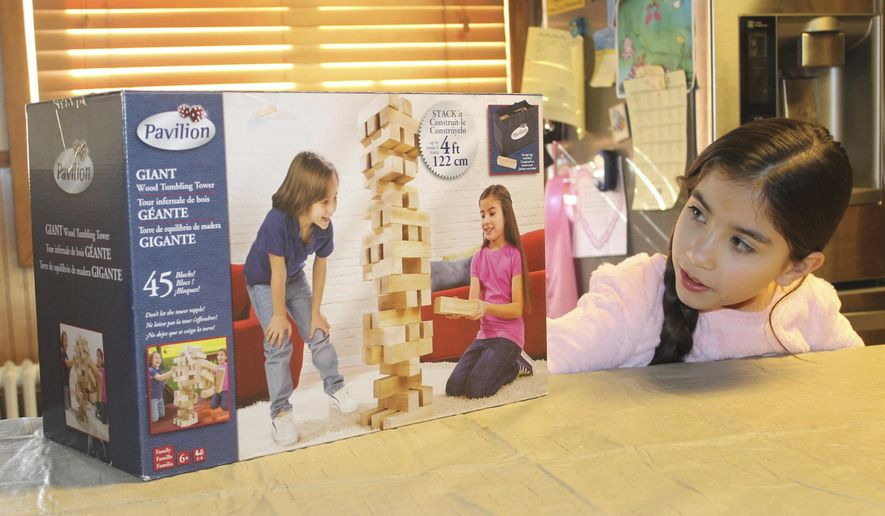 "Mia Michalik of Shenandoah, Pa., looks at the box of a wood tumbling tower game that features here on the front and sides. Pavilion is a line of toys by Toys""R""Us Inc., which Michalik has done other model work. (John E Usalis /Republican-Herald via AP)"