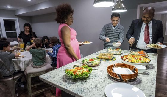 "From left, Marina Aleixo tends to the children's table as Diana Otongo, Umar Choudry and Jonas Mphiri serve themselves a meal of rice, salmon and beef stroganoff inside Aleixo and Choudry's Minneapolis home on March 5, 2017. Immigrants themselves, Aleixo and Choudry are inviting immigrant and refugee families to dinner at their home more frequently. ""These kind of initiatives can help us gain a better understanding of each other,"" Aleixo said.   (Evan Frost/Minnesota Public Radio via AP)"