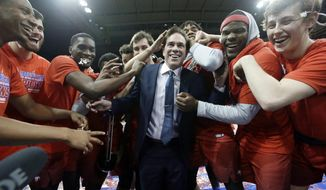 FILE - In this Saturday, March 4, 2017, file photo, SMU head coach Tim Jankovich, center, celebrates with his players after defeating Memphis 103-62 in the American Athletic conference final in Dallas. Jankovich isn't going to complain about a No. 6 seed for the AAC champion with a 16-game winning streak. After being banned from last year's NCAA college basketball tournament despite 25 wins, the Mustangs are happy to be back in the 68-team NCAA field (AP Photo/LM Otero, File)