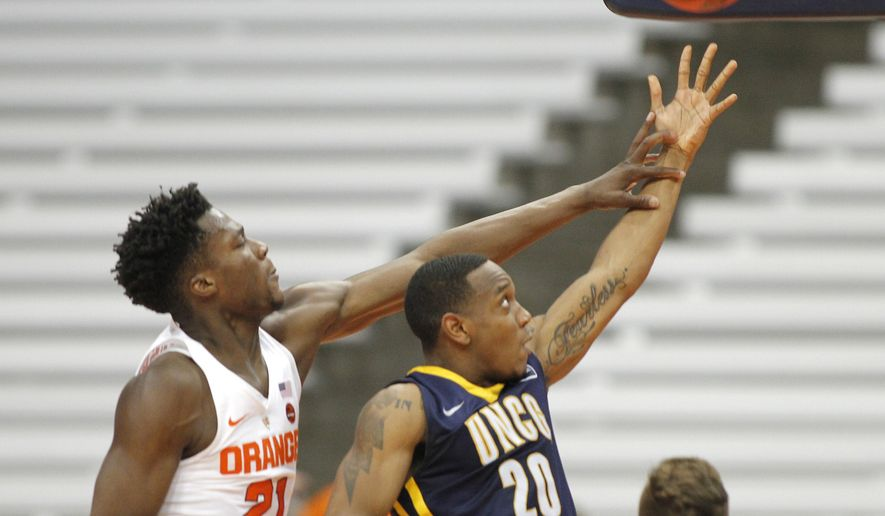 UNC Greensboro's Diante Baldwin, right, shoots under pressure from Syracuse's Tyler Roberson, left, during the second half of an NCAA college basketball game in the NIT in Syracuse, N.Y., Wednesday, March 15, 2017. Syracuse won 90-77. (AP Photo/Nick Lisi)