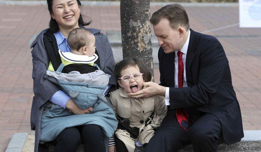 """Robert Kelly, right, a political science professor at Pusan National University, waits for a press conference with his wife Jung-a Kim, left, and children James and Marion, at the university in Busan, South Korea, Wednesday, March 15, 2017. As Kelly speaks from his home office via Skype with BBC about the just-ousted South Korean president, his eyes dart left as he watches on his computer screen as his young daughter parades into the room behind him. Her jaunty entrance resembles the exuberant march of the Munchkins celebrating the Wicked Witch's death in the """"The Wizard of Oz."""" (Ha Kyung-min/Newsis via AP)"""