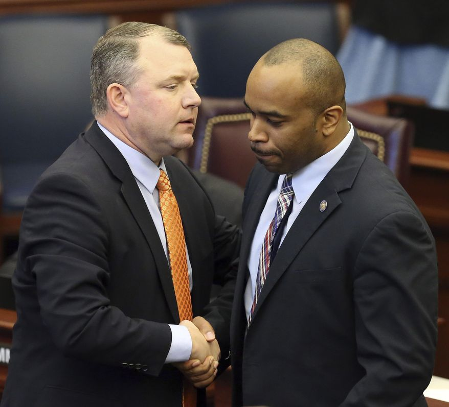 Sen. Bobby Powell, D-West Palm Beach, right, congratulates Sen. Rob Bradley, R-Fleming Island, on the passage of the stand your ground bill during session, Wednesday, March 15, 2017, in Tallahassee, Fla. (AP Photo/Steve Cannon)