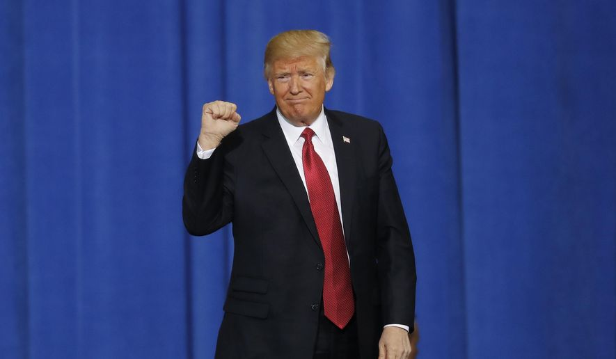 President Donald Trump raises his fist after speaking at the American Center for Mobility, Wednesday, March 15, 2017, in Ypsilanti Township, Mich. (AP Photo/Paul Sancya)