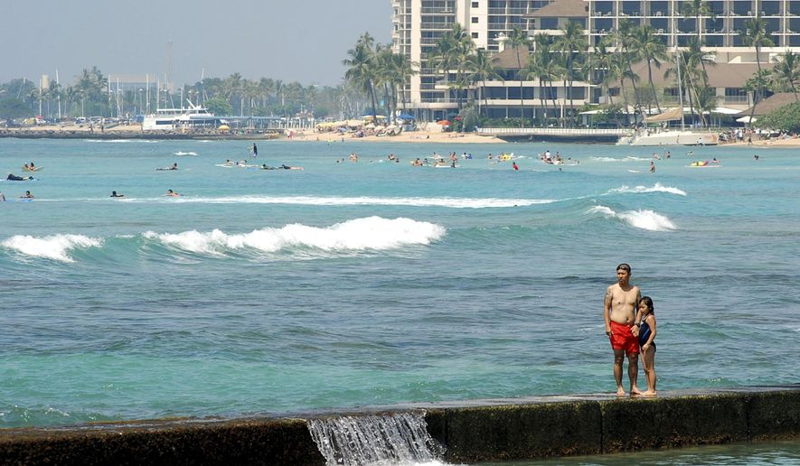 In this Monday, March 13, 2017 photo, people swim off the shore of Waikiki in Honolulu. Hawaii has filed a lawsuit challenging President Donald Trump's revised travel ban, saying the executive order could harm the state's strong tourist economy. (AP Photo/Caleb Jones)