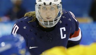 FILE - In this Feb. 17, 2014, file photo, Meghan Duggan of the United States looks up during a face off during the second period of the 2014 Winter Olympics women's semifinal ice hockey game against Sweden at Shayba Arena in Sochi, Russia. The U.S. women's hockey team is threatening to boycott the world championships because of a wage dispute.The team announced Wednesday that they will not participate in the International Ice Hockey Federation tournament that begins March 31, 2017, in Plymouth, Michigan. (AP Photo/Mark Humphrey, File)