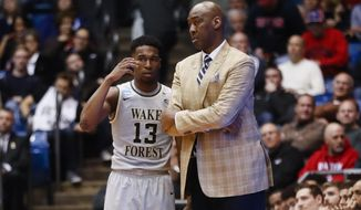 Wake Forest head coach Danny Manning, right, meets with Bryant Crawford (13) by the bench in the second half of a First Four game of the NCAA college basketball tournament against Kansas State, Tuesday, March 14, 2017, in Dayton, Ohio. Kansas won 95-88. (AP Photo/John Minchillo)