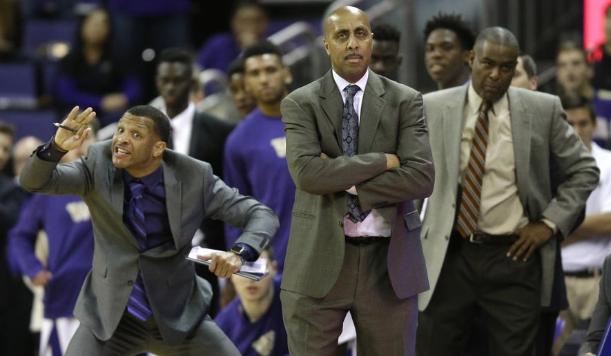 FILE - In this Jan. 18, 2017, file photo, Washington coach Lorenzo Romar, center, stands with assistant coach Michael Porter, right, as assistant coach Will Conroy signals to players during the team's NCAA college basketball game against Colorado in Seattle. Washington announced Wednesday, March 15, 2017, that Romar had been fired after 15 seasons at the school. (AP Photo/Ted S. Warren, file)