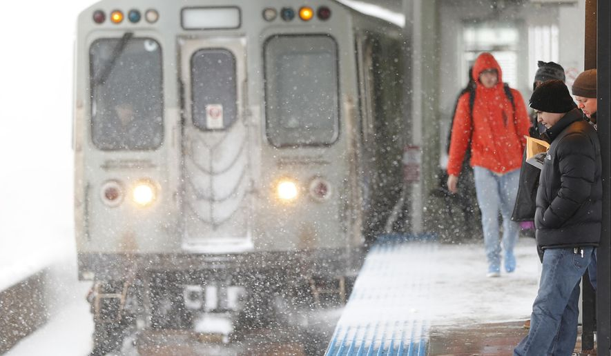 Travelers using the Chicago Transit Authority's Blue Line wait in a warming section of the Montrose Station as a train heading to O'Hare International Airport arrives Tuesday, March 14, 2017, in Chicago. (AP Photo/Charles Rex Arbogast) ** FILE **
