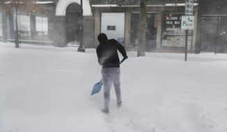 Winds whip through a downtown street as a pedestrian shovels a path for a snowed-in car during a snowstorm in Lewiston, Maine, Tuesday, March 14, 2017. A blustery late-season storm is hitting the Northeast, closing schools and prompting dire warnings to stay off the roads. (AP Photo/David Goldman)