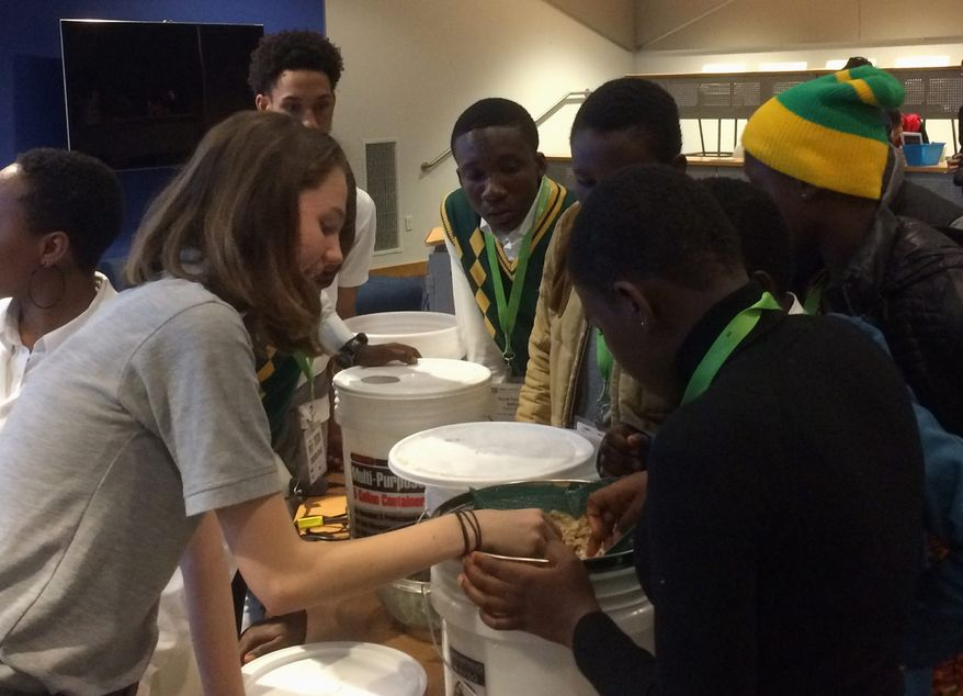 Students from McKinley Technology High School in the District and Winneba High School in Ghana work on their prototype water filtration system, part of a virtual student exchange program focused on STEM education. (Julia Brouillette/The Washington Times)