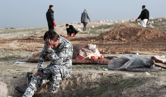An Iraqi policeman collects himself as he is surrounded by bodies at the site of a mass grave containing some two dozen people, many of them children, in an area recently re-taken from Islamic State militants in Mosul, Iraq, Wednesday, March. 15, 2017. (AP Photo/Christian Stephen)