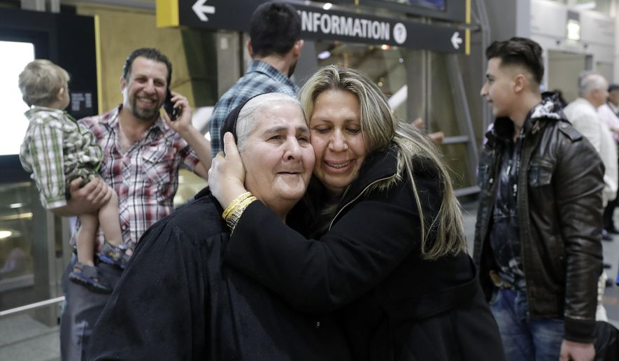 Nadia Hanan Madalo, center right, hugs her mother, Alyshooa Kannah, left, at the airport after arriving from Iraq Wednesday, March 15, 2017, in San Diego. Madalo and her family, refugees forced to flee their town of Batnaya, Iraq, after the Islamic State invaded and destroyed it several years ago, arrived in San Diego to be reunited with Madalo's siblings and mother. As they flew to the U.S. on Wednesday, a federal judge in Hawaii put a hold on President Trump's newest ban - the latest development in a fight between the administration and the courts that has injected more uncertainty into the lives of refugees. (AP Photo/Gregory Bull)
