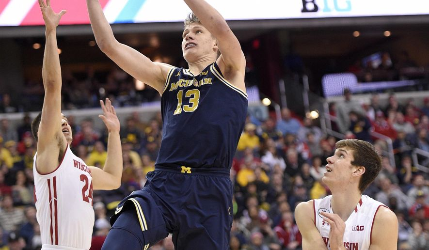 Michigan forward Moritz Wagner (13) goes to the basket against Wisconsin's Bronson Koenig, left, and Ethan Happ, right, during the second half of an NCAA college basketball game for the Big Twn tournament title, Sunday, March 12, 2017, in Washington. Michigan won 71-56. (AP Photo/Nick Wass)