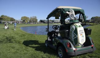 The golf cart and bag belonging to the late golfing great Arnold Palmer sits on a grassy spot next to the 16th tee as Patrick Rodgers hits from the rough alongside the 18th fairway during the first round of the Arnold Palmer Invitational golf tournament in Orlando, Fla., Thursday, March 16, 2017. (AP Photo/Phelan M. Ebenhack)