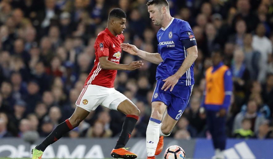 United's Marcus Rashford, left, drives the ball past Chelsea's Gary Cahill during the English FA Cup quarterfinal soccer match between Chelsea and Manchester United at Stamford Bridge stadium in London, Monday, March 13, 2017. (AP Photo/Frank Augstein)