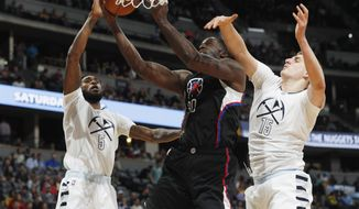 Los Angeles Clippers forward Brandon Bass, center, drives the lane to the basket between Denver Nuggets guard Will Barton, left, and forward Nikola Jokic, of Serbia, in the first half of an NBA basketball game Thursday, March 16, 2017, in Denver. (AP Photo/David Zalubowski)