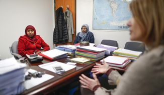 CORRECTS AGE FROM 30 TO 32 - Somalian refugee Ayan Arab, 32, left, listens as Angie Plummer, executive director of Community Refugee and Immigration Services, speaks, Thursday, March 16, 2017, in Columbus, Ohio. Arab hasn't seen her husband in five years but hoped before the bans were issued he'd cleared the hurdles necessary to join her from a camp in Uganda. Columbus has the country's largest percentage of Somali refugees. Some refugees in the city haven't seen spouses, parents or children for years. (AP Photo/John Minchillo)