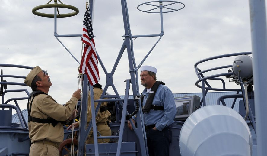 CORRECTS BOAT NUMBER TO 305, NOT 105 - Crew members Bob Wade, left, and Dale Casey, raise an American flag during a media ride Thursday, March 16, 2017, on the PT 305 that was restored by the National WWII Museum, on Lake Pontchartrain, where she was originally tested by Higgins Industries more than 70 years ago, in New Orleans. The U.S. Navy PT boat that sank three vessels and saw action in Europe in World War II is back in New Orleans where it was built, what historians describe as the nation's only fully restored combat ship of that type from the era. Its return to water is the culmination of a 10-year restoration project by the museum. (AP Photo/Gerald Herbert)