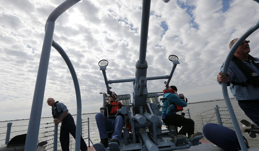 CORRECTS BOAT NUMBER TO 305, NOT 105 - Members of the media sit on a gun turret during a media ride Thursday, March 16, 2017, on the PT 305, which was restored by the National WWII Museum, on Lake Pontchartrain, where she was originally tested by Higgins Industries more than 70 years ago, in New Orleans, Thursday, March 16, 2017. The U.S. Navy PT boat that sank three vessels and saw action in Europe in World War II is back in New Orleans where it was built, what historians describe as the nation's only fully restored combat ship of that type from the era. Its return to water is the culmination of a 10-year restoration project by the museum. (AP Photo/Gerald Herbert)