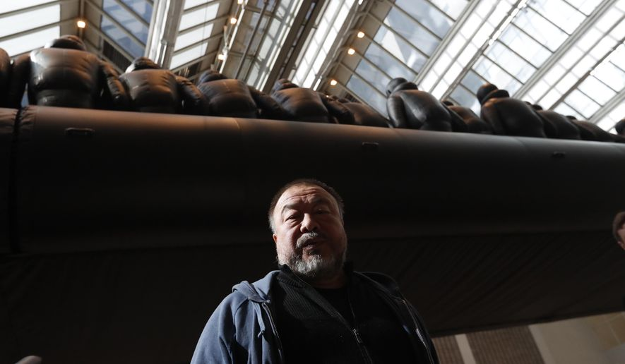 "Chinese activist and artist Ai Weiwei poses by his installation displayed at the National Gallery in Prague, Czech Republic, Thursday, March 16, 2017. A 70-metre-long inflatable boat with life-size figures of 258 refugees prepared for the gallery, called ""The Law of the Journey,"" is one of the artists biggest work of art so far. (AP Photo/Petr David Josek)"
