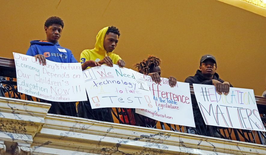 Students holds up signs, joining several hundred parents, educators, education activists, and a handful of legislators in an education rally at the Capitol in Jackson, Miss., Thursday, March 16, 2017. Advocates for public schools are opposing legislative leaders' plans to rewrite the state's school funding formula. (AP Photo/Rogelio V. Solis)