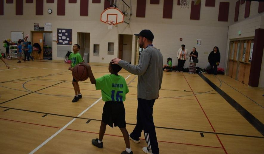 ADVANCE FOR WEEKEND EDITIONS - In this March 15, 2017, photo, Dennis Roushia, coaches practice at Julian Thomas Elementary School in Racine, Wis. The team is co-ed and mixed with fourth and fifth-graders. (Ricardo Torres/The Journal Times via AP)