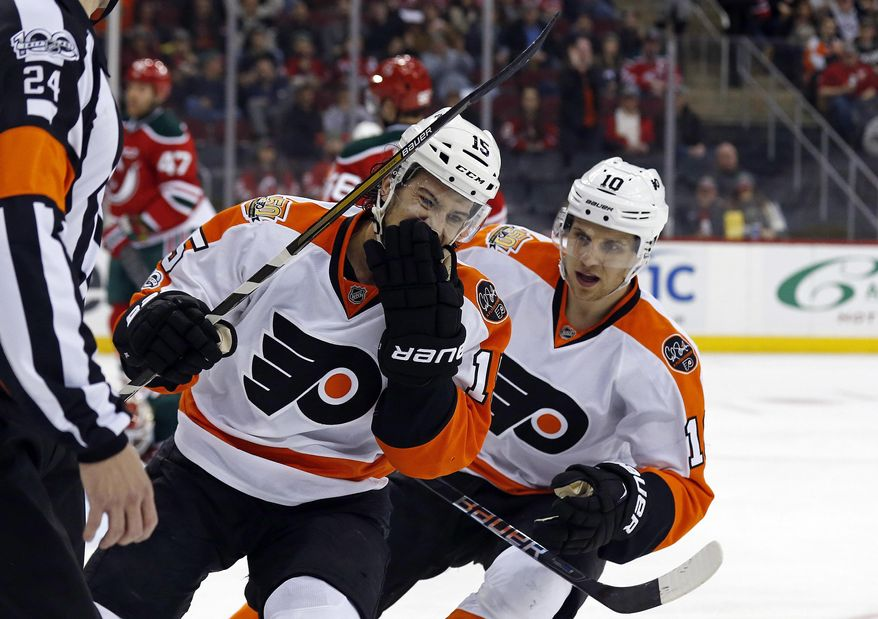 Philadelphia Flyers defenseman Michael Del Zotto (15) is congratulated after scoring a goal by Flyers center Brayden Schenn (10) against the New Jersey Devils during the first period of an NHL hockey game, Thursday, March 16, 2017, in Newark, N.J. (AP Photo/Adam Hunger)
