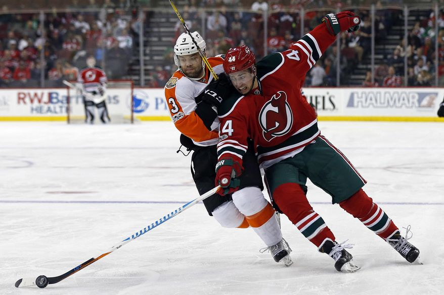 New Jersey Devils left wing Miles Wood (44) battles for the puck with Philadelphia Flyers defenseman Radko Gudas (3) during the second period of an NHL hockey game, Thursday, March 16, 2017, in Newark, N.J. (AP Photo/Adam Hunger)