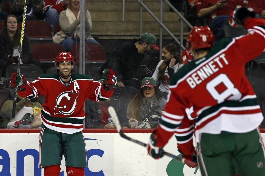 New Jersey Devils center Adam Henrique (14) celebrates scoring a goal with Devils right wing Beau Bennett (8) during the second period of an NHL hockey game against the Philadelphia Flyers, Thursday, March 16, 2017, in Newark, N.J. (AP Photo/Adam Hunger)