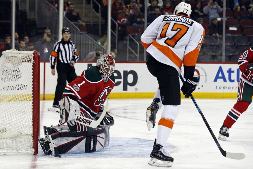 New Jersey Devils goalie Keith Kinkaid (1) makes a save in front of Philadelphia Flyers right wing Wayne Simmonds (17) during the first period of an NHL hockey game, Thursday, March 16, 2017, in Newark, N.J. (AP Photo/Adam Hunger)