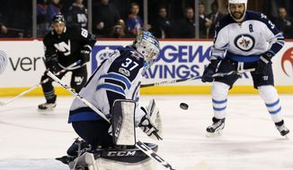Winnipeg Jets goalie Connor Hellebuyck (37) blocks a shot as Winnipeg Jets defenseman Dustin Byfuglien (33) watches during the second period of an NHL hockey game against the New York Islanders, Thursday, March 16, 2017, in New York, (AP Photo/Kathy Willens)