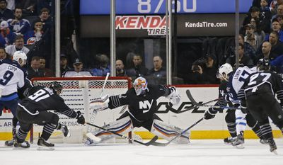 Winnipeg Jets center Adam Lowry (17) scores as the puck sails beyond the reach of New York Islanders goalie Thomas Greiss (1) of Germany with Islanders center John Tavares (91) trying in vain to block it during the second period of an NHL hockey game, Thursday, March 16, 2017, in New York, (AP Photo/Kathy Willens)