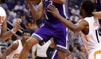 Sacramento Kings forward Skal Labissiere (3) rebounds as Phoenix Suns guard Ronnie Price (14) looks on during the first half of an NBA basketball game, Wednesday, March 15, 2017, in Phoenix. (AP Photo/Matt York)