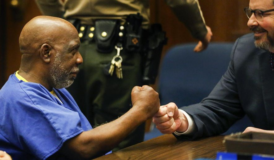 Andrew Wilson, left, exchanges a fist bump with his attorney Adam Grant at the start of a hearing in Los Angeles Superior Court on Wednesday, March 15, 2017 in Los Angles.  Judge Laura Priver ordered the release of Wilson, who spent more than three decades in prison for murder after prosecutors conceded he did not get a fair trial.    (Mark Boster/Los Angeles Times via AP, Pool)