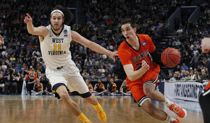 West Virginia Nathan Adrian (11) chases Bucknell forward Zach Thomas (23) during the first half of a first-round college basketball game in the NCAA Tournament, Thursday, March 16, 2017, in Buffalo, N.Y. (AP Photo/Jeffrey T. Barnes)