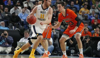 West Virginia forward Nathan Adrian (11) drives against Bucknell forward Zach Thomas (23) during the first half of a first-round college basketball game in the NCAA Tournament, Thursday, March 16, 2017, in Buffalo, N.Y. (AP Photo/Jeffrey T. Barnes)
