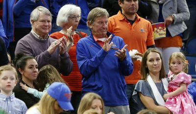 Former Florida football coach Steve Spurrier, center claps during team introductions before the start of a game between Florida and East Tennessee State in the first round of the NCAA college basketball tournament, Thursday, March 16, 2017 in Orlando, Fla. (AP Photo/Wilfredo Lee)