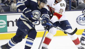 Columbus Blue Jackets' Jack Johnson, left, tries to clear the puck away from Florida Panthers' Jaromir Jagr, of the Czech Republic, during the third period of an NHL hockey game Thursday, March 16, 2017, in Columbus, Ohio. The Blue Jackets beat the Panthers 2-1. (AP Photo/Jay LaPrete)