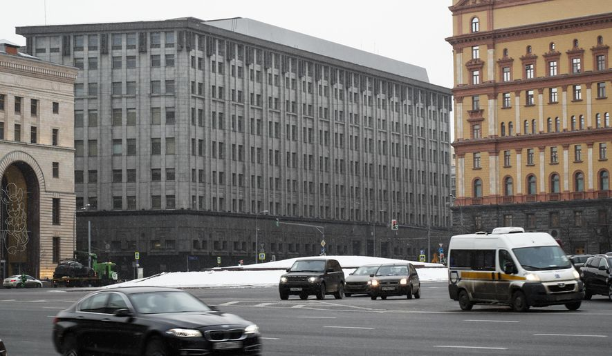 FILE - In this Friday, Dec. 30, 2016 file cars pass the FSB headquarters in downtown Moscow, Russia. A U.S. indictment of two Russian intelligence agents and two hackers alleged to have stolen more than half a billion U.S. email accounts in 2014 has shone a spotlight on the intertwining of the Russian security services and the murky digital underworld. The intelligence officers of the powerful FSB, Russia's Federal Security Service, are accused of employing cybercriminals to access Yahoo's systems and steal data on millions of ordinary users as well as U.S. and Russian officials, Russian journalists and executives at large private companies. (AP Photo/Alexander Zemlianichenko, file)