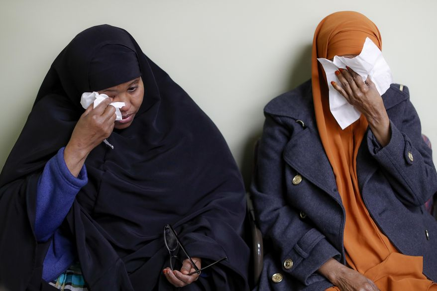 Somali refugees Layla Muali, left, and Hawo Jamile, right, wipe away tears during an interview at the Community Refugee & Immigration Services offices, Thursday, March 16, 2017, in Columbus, Ohio.  Somali refugees in Ohio continue their wait for overseas relatives amid uncertainty created by the proposed White House travel ban and new court decisions blocking that ban. Columbus has the country's largest percentage of Somali refugees(AP Photo/John Minchillo)