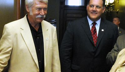 FILE - In this July 29, 2009, file photo, then-women's gymnastics coach Bela Karolyi, left, and USA gymnastics president Steve Penny talk in a hallway of the State Capitol in Hartford, Conn. Penny resigned as president of USA Gymnastics on Thursday, March 16, 2017, following intensified pressure on the organization for its handling of sex abuse cases.  (AP Photo/George Ruhe, File)