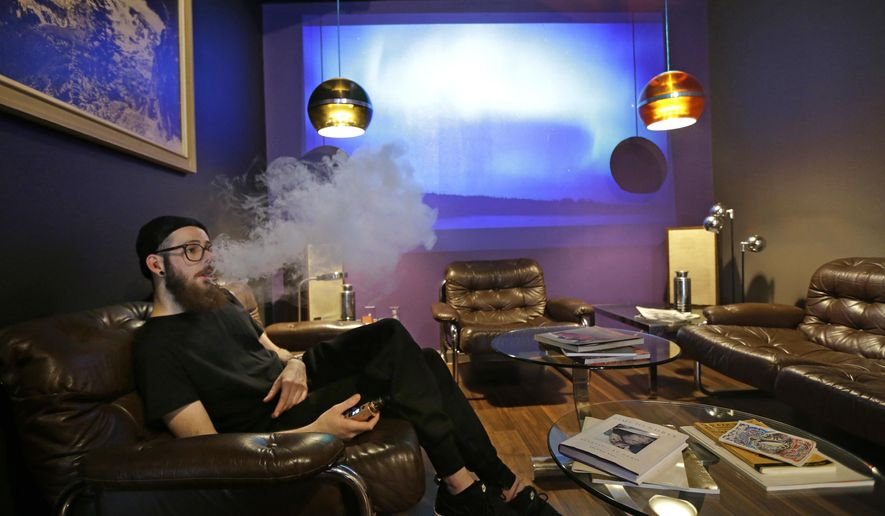 In this March 15, 2017, photo, Cameron Fletcher, an employee at the Future Vapor store in Seattle, vapes as he takes a break in the store's lounge. Lawmakers in the Washington state Legislature are proposing a tax on vapor products, e-cigarettes and other nicotine products. (AP Photo/Ted S. Warren)