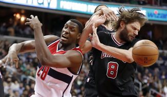 Washington Wizards center Ian Mahinmi (28), from France, and Chicago Bulls center Robin Lopez (8) go for the rebound during the second half of an NBA basketball game Friday, March 17, 2017, in Washington. (AP Photo/Alex Brandon)