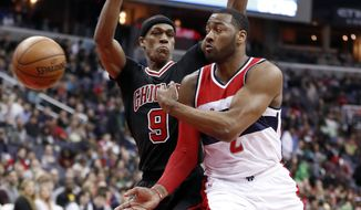Washington Wizards guard John Wall (2) passes the ball past Chicago Bulls guard Rajon Rondo (9) during the first half of an NBA basketball game Friday, March 17, 2017, in Washington. (AP Photo/Alex Brandon)