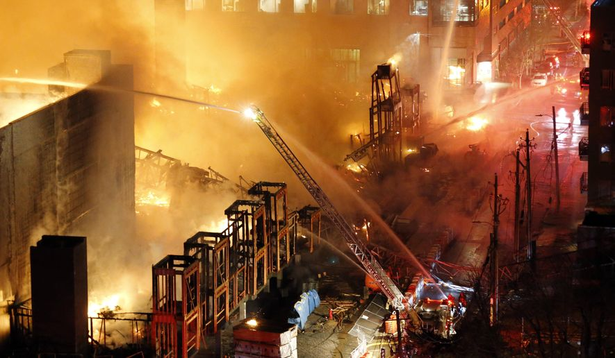 Firefighters battle a five-alarm fire burning an apartment building and surrounding structures in downtown Raleigh, N.C., Thursday night, March 16, 2017. Fire was consuming an apartment building under construction. The cause of the fire is under investigation. (Chris Seward/The News & Observer via AP)