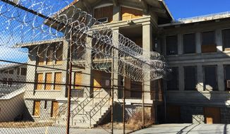 In this March 3, 2017 photo, razor wire is coiled along a fence at the closed Mount McGregor Correctional Facility in Wilton, N.Y. Perched atop an Adirondack mountain, the 325-acre site for sale seems to have everything a developer could want: spectacular views, a man-made lake, close proximity to the tourist destination of Saratoga Springs and, oh, former President Ulysses S. Grant lived out his final days in a home next door. States are finding out the hard way that closed prisons can be a tough sell. (AP Photo/Chris Carola)