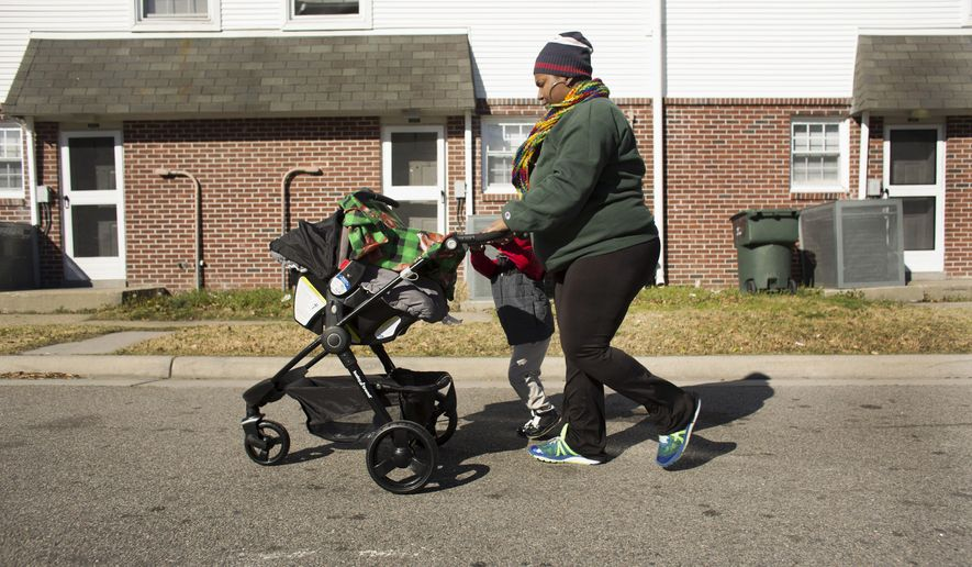 ADVANCE FOR SUNDAY, MARCH 19, 2017 - In this Feb. 13, 2017 photo, without the use of her car Tamaia Camp walks with two of her children, three month old Devon Smith and three-year-old Meki Camp, to pickup six-year-old Mekel Camp from school, in Norfolk, Va. Camp is being charged nearly $19,000 in tolls and late fees from Elizabeth River Crossings (L. Todd Spencer/The Virginian-Pilot via AP)