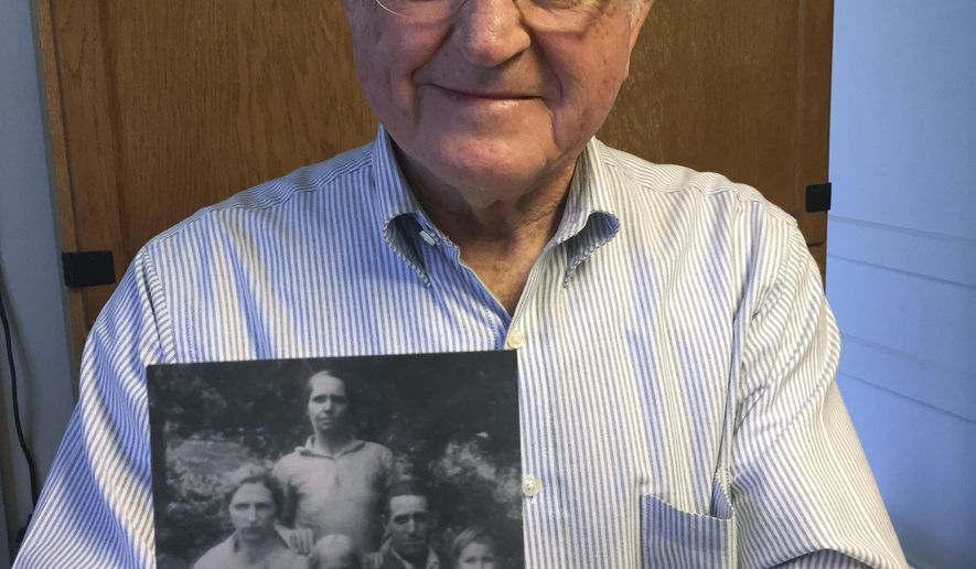 ADVANCE FOR MONDAY MARCH 20 AND THEREAFTER - In a March 12, 2017 photo, Sherman Shifflett, of Louisa County, Va., whose family was displaced from their home in the mountains of Rockingham County by the creation of Shenandoah National Park,  holds a photo of his family when they lived on what is now park land. His family included his mother and father, seated, Nelie and Harvey Shifflett, siblings Ed, on his mother's lap, Bulah standing in between her parents, and Ferrell, on his father's lap, and aunt Polly Morris, standing behind. Bill Henry founded the nonprofit Blue Ridge Heritage Project to honor those displaced by the creation of the Shenandoah National Park in the 1920s and 1930s.  (Bill Lohmann/Richmond Times-Dispatch via AP)