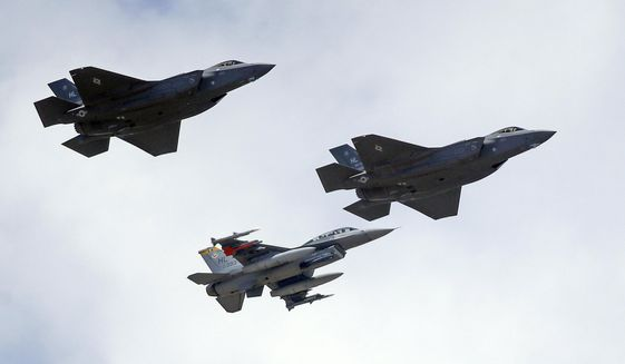 This Sept. 2, 2015, file photo shows an F-16, below, escorting two F-35 jets, above, after arriving the latter arrived at Hill Air Force Base in Utah. The U.S. and its Asia-Pacific allies are rolling out their new stealth fighter jet, a cutting-edge plane that costs about $100 million each. (AP Photo/Rick Bowmer, File)
